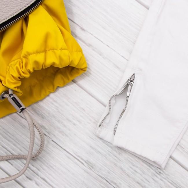Dettagli outfit casual, jeans bianchi e tendenza multicolor.